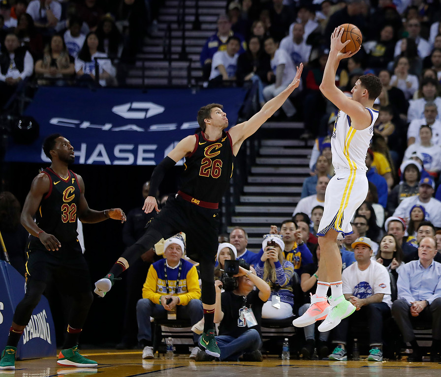 . Golden State Warriors guard Klay Thompson (11) shoots over Cleveland Cavaliers guard Kyle Korver (26) during the first half of an NBA basketball game in Oakland, Calif., Monday, Dec. 25, 2017. (AP Photo/Tony Avelar)