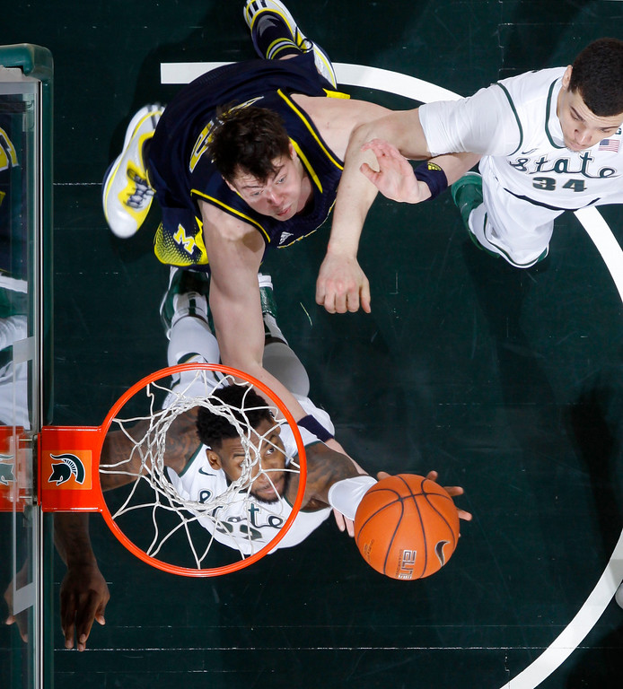 . Michigan State\'s Branden Dawson, bottom left, and Gavin Schilling (34) and Michigan\'s Ricky Doyle reach for a rebound during the second half of an NCAA college basketball game, Sunday, Feb. 1, 2015, in East Lansing, Mich. Michigan State won 76-66 in overtime. (AP Photo/Al Goldis)