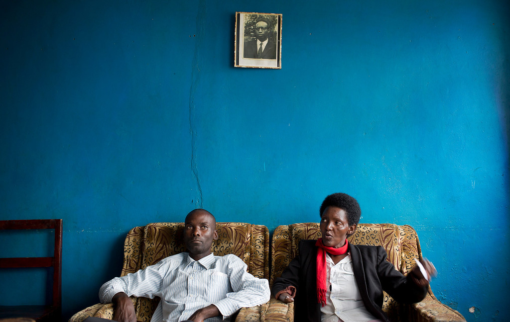 . In this photo taken Wednesday, March 26, 2014, Emmanuel Ndayisaba, left, and Alice Mukarurinda, recount their experiences of the Rwandan genocide as they sit under a photograph of Alice\'s father, who was elsewhere at the time and also managed to survive, at Alice\'s house in Nyamata, Rwanda. She lost her baby daughter and her right hand to a manic killing spree. He wielded the machete that took both. Yet today, despite coming from opposite sides of an unspeakable shared past, Alice Mukarurinda and Emmanuel Ndayisaba are friends. She is the treasurer and he the vice president of a group that builds simple brick houses for genocide survivors. They live near each other and shop at the same market. Their story of ethnic violence, extreme guilt and, to some degree, reconciliation is the story of Rwanda today, 20 years after its Hutu majority killed more than 1 million Tutsis and moderate Hutus. The Rwandan government is still accused by human rights groups of holding an iron grip on power, stifling dissent and killing political opponents. But even critics give President Paul Kagame credit for leading the country toward a peace that seemed all but impossible two decades ago. (AP Photo/Ben Curtis)