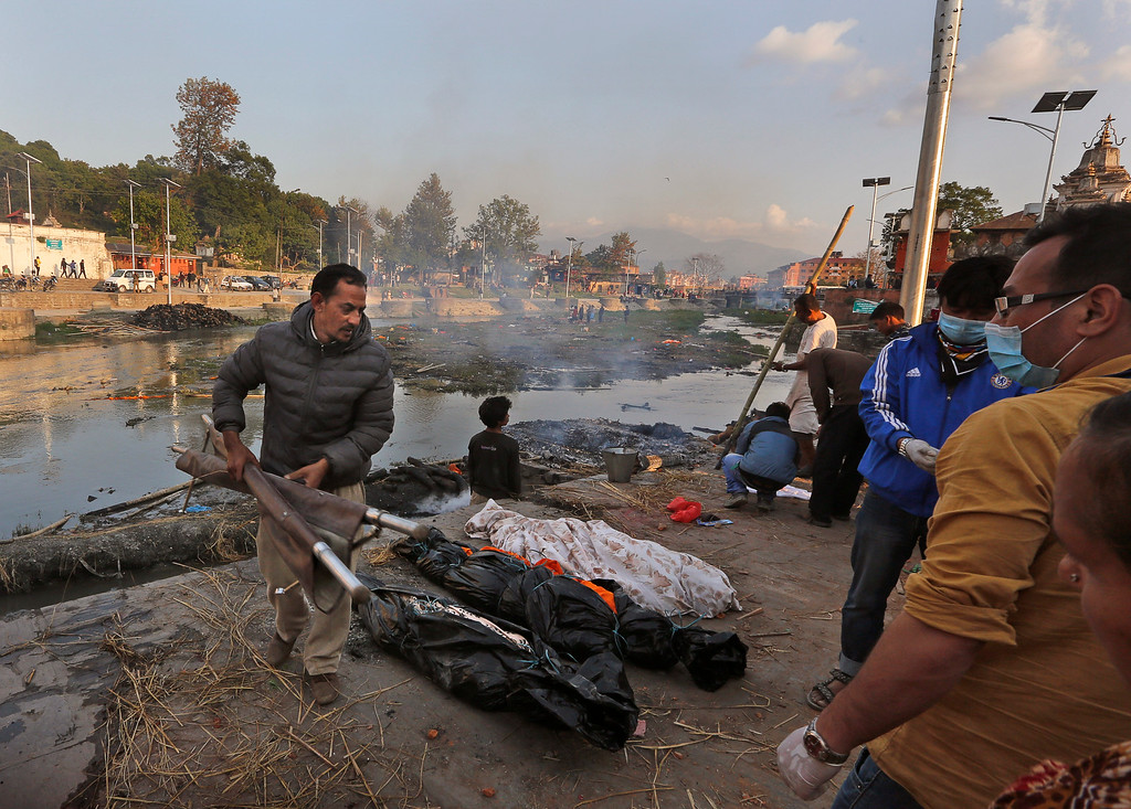. In this Tuesday, April 28, 2015 photo, Shankar Pradhan, left, brings bodies of his family members who died in Saturday\'s massive earthquake for cremation at a ghat on the banks of Bagmati River near the Pashupatinath Temple in Kathmandu, Nepal. The ancient Hindu cremation rite is meant to purify souls for the afterlife, and this was far from the only one for Pradhan and his extended family. When the quake crumpled his brotherís four-story house into a cloud of dust on April 25, it left them with a total of 18 souls to prepare. (AP Photo/Manish Swarup)