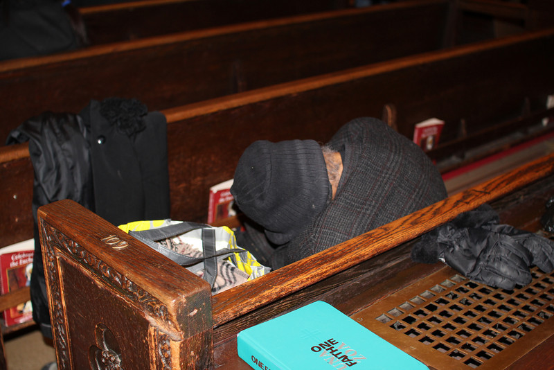 homeless woman inside St. Patrick's Cathedral - gloves drying on heater