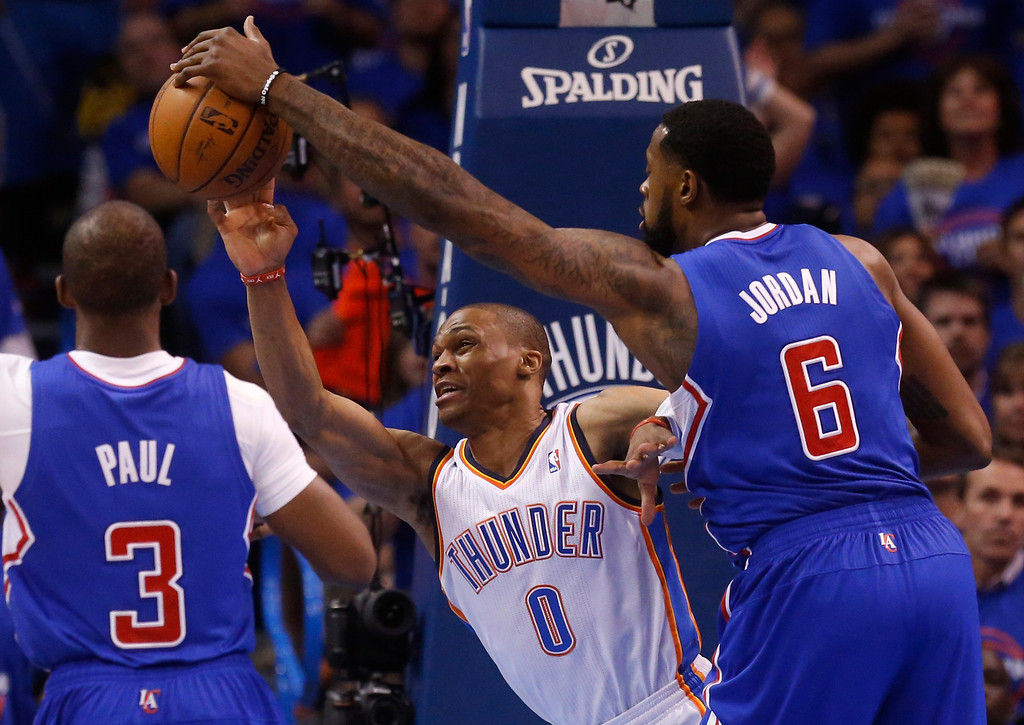 . Los Angeles Clippers center DeAndre Jordan (6) blocks a pass by Oklahoma City Thunder guard Russell Westbrook (0) in the first quarter of Game 1 of the Western Conference semifinal NBA basketball playoff series in Oklahoma City, Monday, May 5, 2014. (AP Photo/Sue Ogrocki)