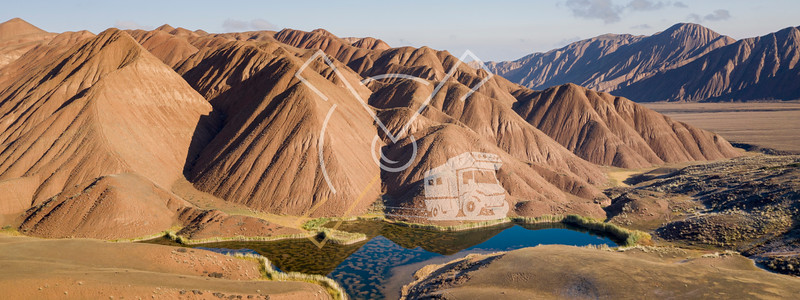 aerial landscape of the amazing Ozero Torpo, a lake surrounded by eroded mud hills along the Mels-Ashu pass connection Tash-Rabat at the village of Baetov