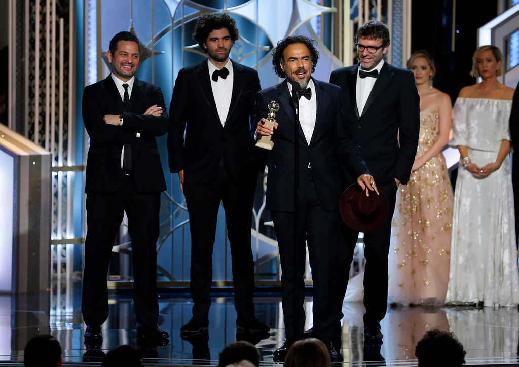 ". In this image released by NBC,  Alejandro Gonzalez Inarritu, accepts the award  for best screenplay for ""Birdman,\""with Alexander Dinelaris, background from left, Armando Bo, and Nicolas Giacobone at the 72nd Annual Golden Globe Awards on Sunday, Jan. 11, 2015, at the Beverly Hilton Hotel in Beverly Hills, Calif. (AP Photo/NBC, Paul Drinkwater)"