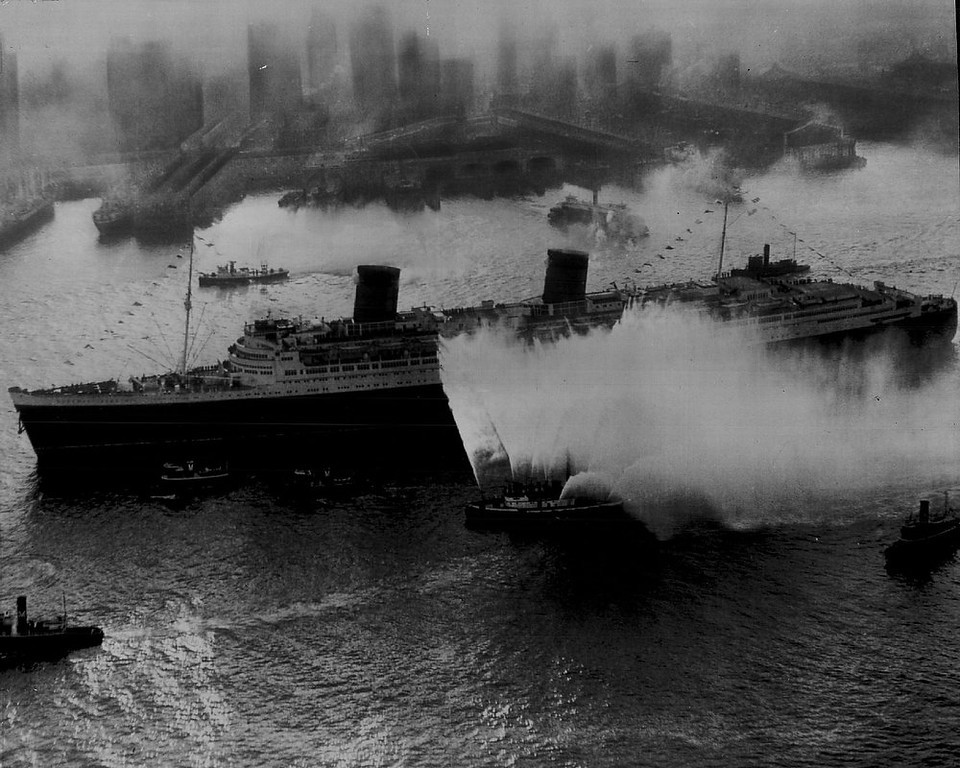 . The Largest Ship Afloat has doffed her drab wartime uniform arriving in the New York harbor from England in bright peacetime dress of red, white and black on Oct. 22, 1946. She is the British luxury liner Queen Elizabeth, shown here being greeted by fireboats throwing water, and tugs blowing whistles. It was the first peacetime trip of the 83,673-ton former troop carrier. Queen Elizabeth