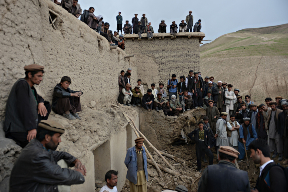 . Afghan villagers look on as rescuers search desperately for survivors trapped under the mud in Argo district of Badakhshan province on May 3, 2014 after a massive landslide May 2 buried a village. Rescuers searched in vain for survivors May 3 after a landslide buried an Afghan village, killing 350 people and leaving thousands of others feared dead amid warnings that more earth could sweep down the hillside. Local people made desperate efforts to find victims trapped under a massive river of mud that engulfed Aab Bareek village in Badakhshan province, where little sign remained of hundreds of destroyed homes. (SHAH MARAI/AFP/Getty Images)