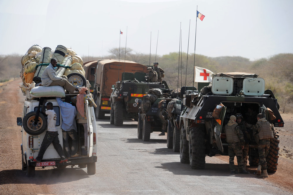 Description of . A local truck passes by a convoy of French army vehicules heading toward Gao on February 7, 2013 on the road from Gossi. Four Malian civilians were killed by a landmine in territory reclaimed from Islamist rebels, police said as France mulled handing over its four-week-old intervention to UN peacekeepers. PASCAL GUYOT/AFP/Getty Images