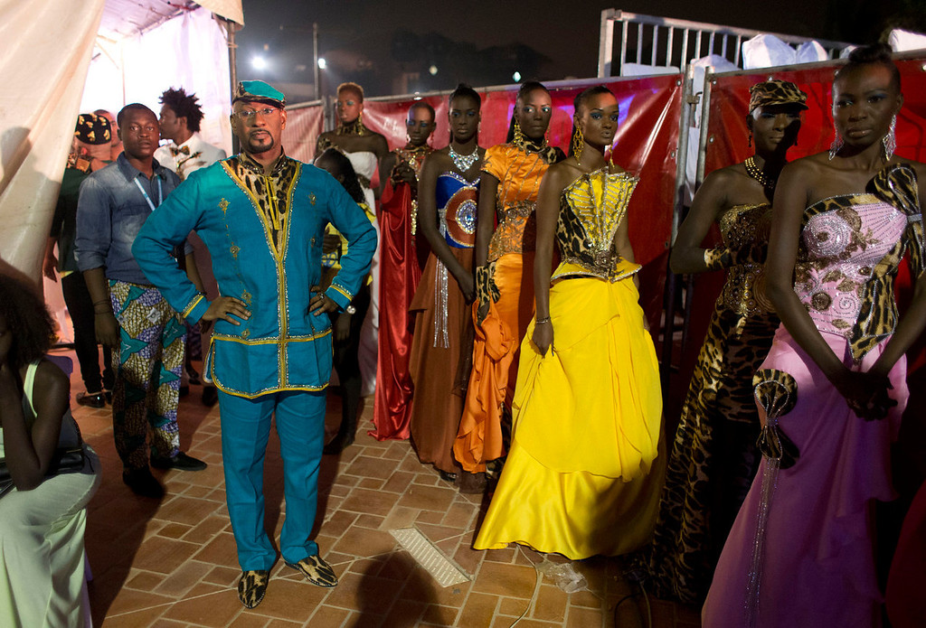 . Designer Habib Sangare, front left, looks on as models wearing his creations wait to walk the runway, at Hotel des Almadies, in Dakar, Senegal, on Saturday, June 22, 2013. After a Friday show held in a dusty marketplace in the working class suburb of Guediawaye, the runway finale of Dakar Fashion Week was held at a luxury hotel and showcased the work of 14 designers from West Africa, Europe, South America, and the Caribbean. (AP Photo/Rebecca Blackwell)