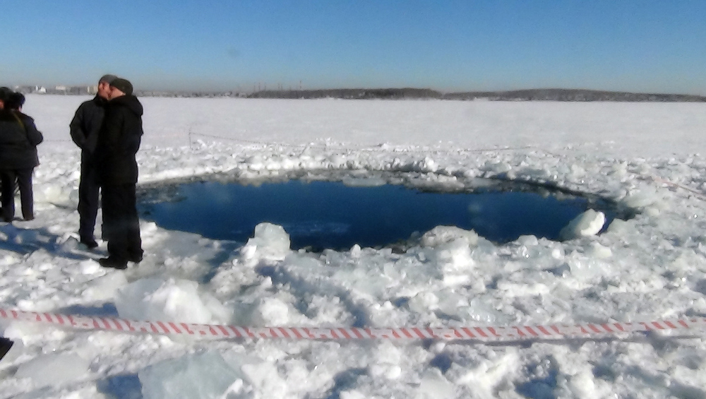 Description of . A handout photo taken on February 15, 2013, and provided by Chelyabinsk region police department shows people standing near a six-metre (20-foot) hole in the ice of a frozen lake, reportedly the site of a meteor fall, outside the town of Chebakul in the Chelyabinsk region. A plunging meteor exploded today with a blinding flash above central Russia, setting off a shock wave that shattered windows and hurt over 500 people in an event unprecedented in modern times. The office of the local governor said in a statement that a meteorite had fallen into a lake outside the town of Chebakul in the Chelyabinsk region.  AFP PHOTO /  CHELYABINSK REGION POLICE DEPARTMENT