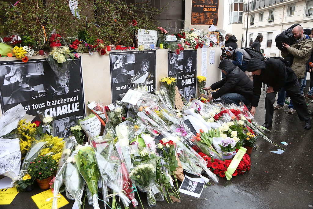 . Flowers are left close to the Charlie Hebdo offices on a day of mourning following a terrorist attack at the satirical newspaper building on January 8, 2015 in Paris, France. Twelve people were killed including two police officers as two gunmen opened fire at the offices of the French satirical publication Charlie Hebdo on January 7.   (Photo by Marc Piasecki/Getty Images)