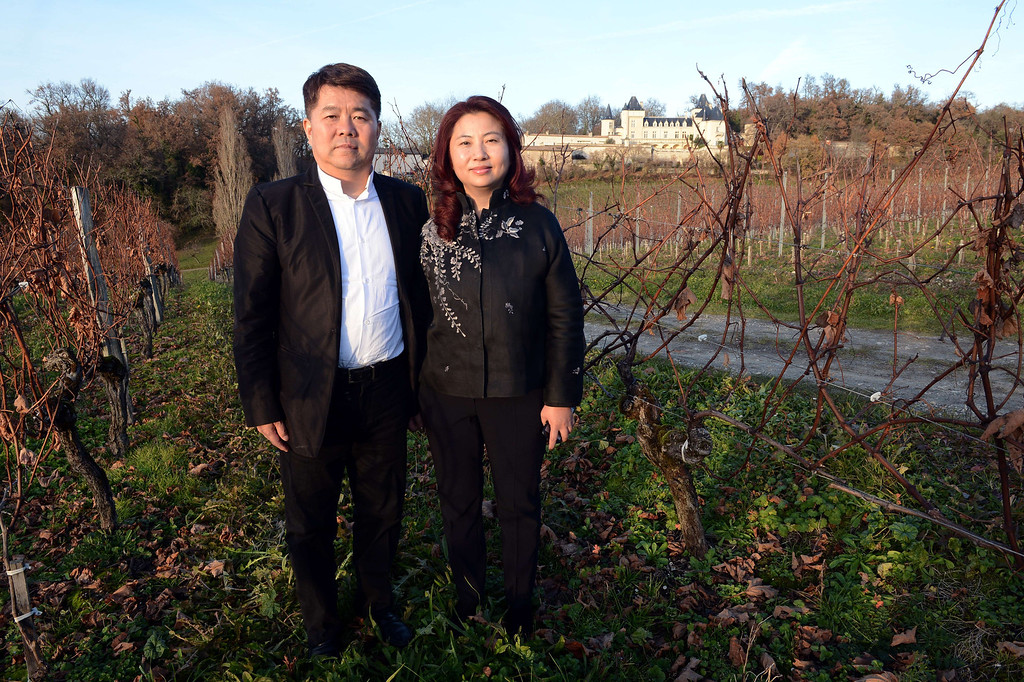 . Chinese billionaire Lam Kok (L) and his spouse pose for a photograph on December 20, 2013, in the Chateau de la Rivière vineyard, in La Riviere.  This photograph was taken less than an hour before the crash. AFP PHOTO / MEHDI FEDOUACH/AFP/Getty Images