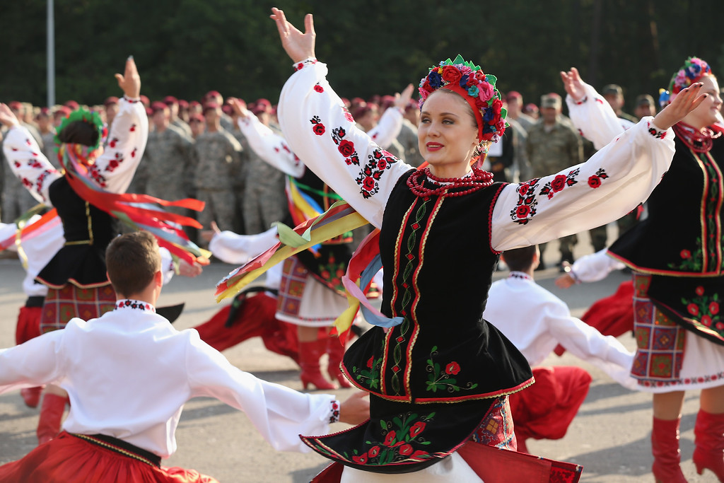". Members of the U.S. Army 173rd Airborne Brigade stand at attention as a Ukrainian folk dance group performs at the opening ceremony of the ""Rapid Trident\"" NATO military exercises on September 15, 2014 near Yavorov, Ukraine.   (Photo by Sean Gallup/Getty Images)"