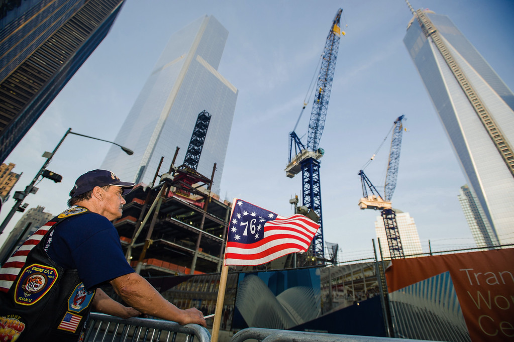 . Jose Gonzales, of New York, takes a minute to reflect in front of One World Trade Center, right, during the 12th anniversary observance of the 9/11 terror attacks, Wednesday, Sept. 11, 2013 in New York.   (AP Photo/Lauren Casselberry)