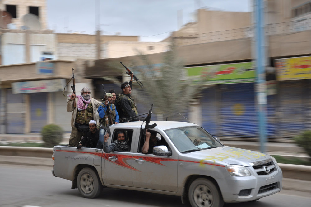 . Free Syrian Army fighters carry their weapons and cheer as they drive in the northeastern provincial capital of Raqqa after capturing it, March 4, 2013. Opposition sources and residents said rebel fighters captured Raqqa on Monday and toppled a statue of President Bashar al-Assad\'s father, in what would be the first major city to be captured since the revolt erupted against four decades of Assad family rule in March 2011. Picture taken March 4, 2013. REUTERS/Mohamed Al-Husain/Shaam News Network/Handout