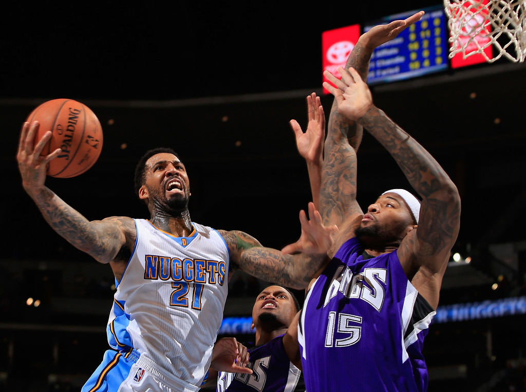 . DENVER, CO - NOVEMBER 03:  Wilson Chandler #21 of the Denver Nuggets tries to get off a shot against DeMarcus Cousins #15 of the Sacramento Kings at Pepsi Center on November 3, 2014 in Denver, Colorado. The Kings defeated the Nuggets 110-105. NOTE TO USER: User expressly acknowledges and agrees that, by downloading and or using this photograph, User is consenting to the terms and conditions of the Getty Images License Agreement.  (Photo by Doug Pensinger/Getty Images)