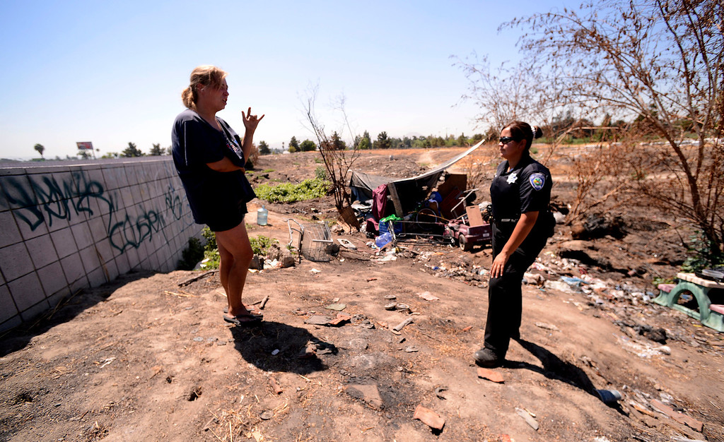 . Dawna Bonner, 30, speaks with San Bernardino Police Officer and Homeless Advocate Sochilt Martinez outside a homeless camp along Ninth Street in San Bernardino August 14, 2013. GABREL LUIS ACOSTA/STAFF PHOTOGRAPHER.