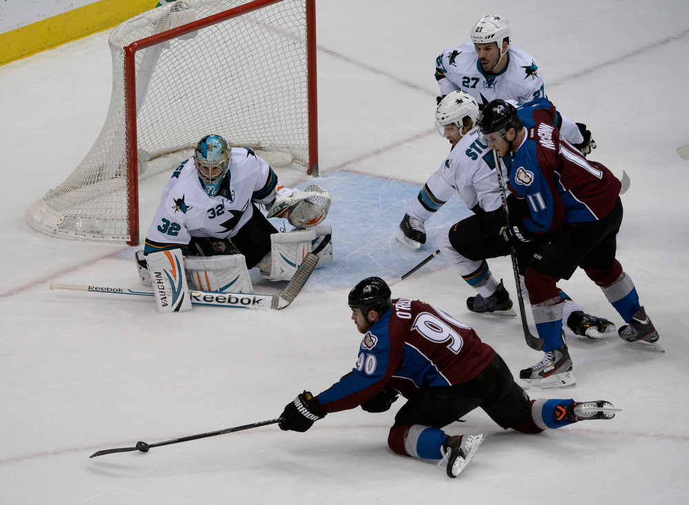 . Colorado Avalanche center, Ryan O\'Reilly, bottom right, gathers a lose puck in front of San Jose Sharks goalie, Alex Stalock\'s net in the first period of play at the Pepsi Center Saturday afternoon, March 29, 2014. (Photo By Andy Cross / The Denver Post)