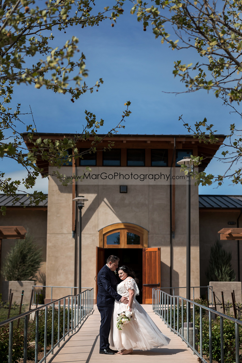 full body portrait of bride and groom looking at each other in front of the main entrance to Livermore Garre Vineyard and Winery