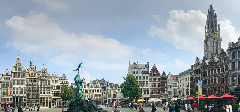 Grote Markt (Market Square) lined with 19th century guildhouses on the left. The spire of the 16th century Cathedral of Our Lady looms on the right.