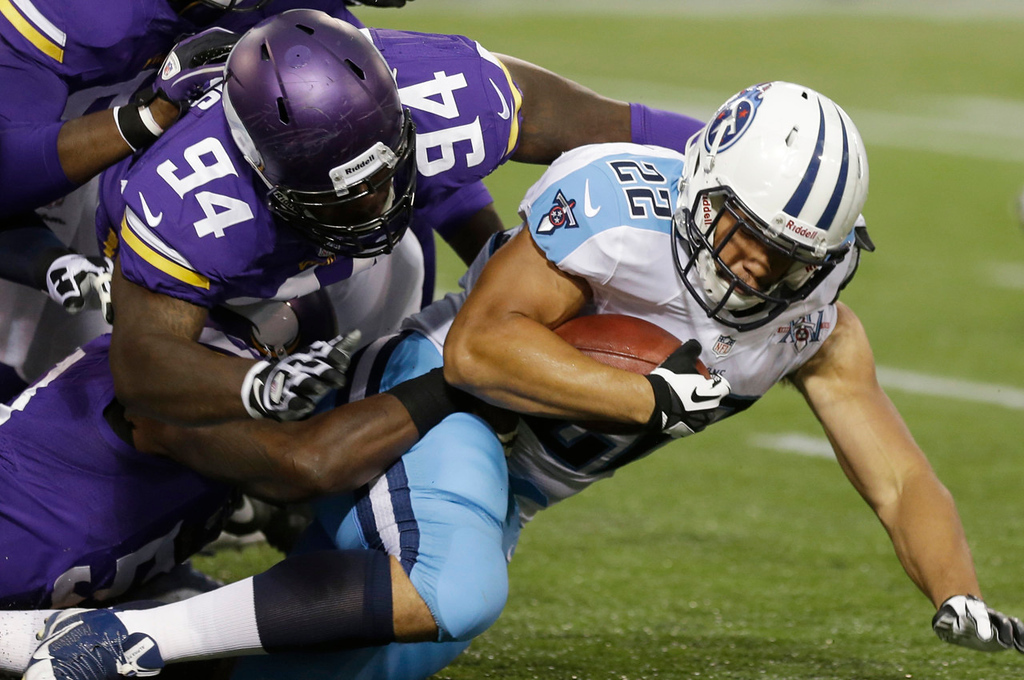 . Titans running back Jackie Battle, right, is tackled by Vikings defensive end Lawrence Jackson during the first quarter. (AP Photo/Jim Mone)