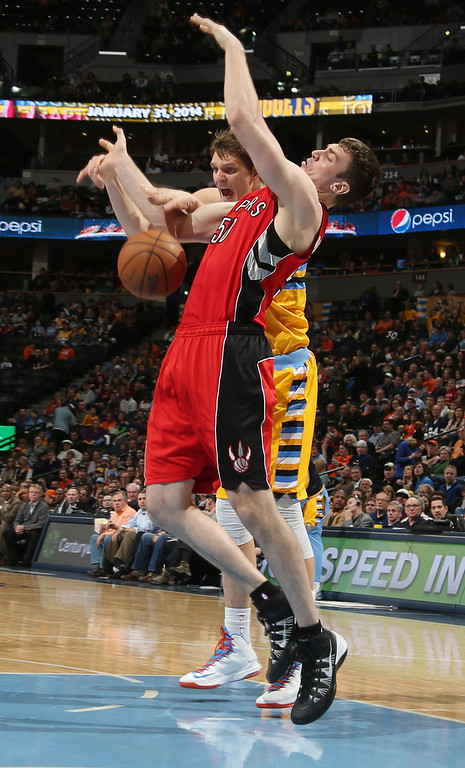 . Toronto Raptors center Tyler Hansbrough, front, becomes entangled with Denver Nuggets center Timofey Mozgov, of Russia, as he drives lane for a shot in the third quarter of an NBA basketball game in Denver, Friday, Jan. 31, 2014. (AP Photo/David Zalubowski)