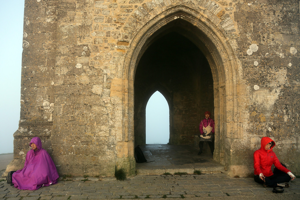 . Visitors to Glastonbury Tor meditate beside St. Michael\'s Tower, a ruined 14th-century church tower, as the sun rises and begins to clear the early morning mist and fog near the town of Glastonbury on September 4, 2013 in Somerset, England.  (Photo by Matt Cardy/Getty Images)