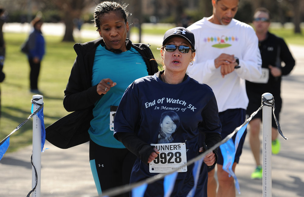. Denver Police Sargeant Betty Hale, left, finishes the race with friends.  Family, colleagues, and friends of slain Denver Police Officer Celena Hollis turned out April 7, 2013 for a 5k run and walk to raise money for a scholarship fun and a memorial bench in City Park in Denver, CO.  Over 300 runners and walkers participated in the race that started at 9:00 am.  The race looped around City Park.  After the race, a gathering was held to remember Hollis and 22 white doves were released in her memory.  (Photo By Helen H. Richardson/ The Denver Post)
