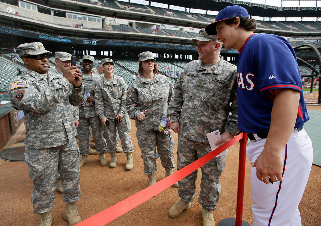 . Texas Rangers\' Derek Holland, right, poses with U.S. Army soldiers of the 300th Sustainment Brigade of Grand Prairie, Texas, before a baseball game against the Philadelphia Phillies, Monday, March 31, 2014, in Arlington, Texas. (AP Photo/Tony Gutierrez)