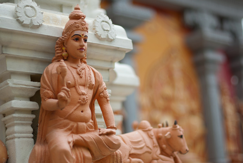 Small Hindu statue on foreground at pagoda in Singapore