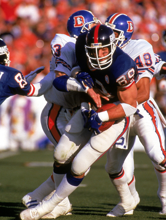 . Tight end Mark Bavaro #89 of the New York Giants fights for yardage against defensive backs Steve Foley #43 and Dennis Smith #49 of the Denver Broncos during Super Bowl XXI at the Rose Bowl on January 25, 1987 in Pasadena, California.  (Photo by George Rose/Getty Images)