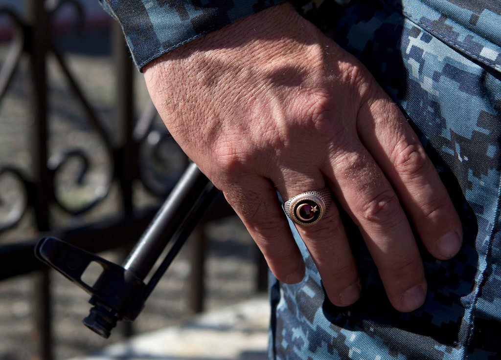 . A policeman wears a ring showing the Islamic symbol of the star and crescent, as the barrel of a rifle is seen in the background, in the Chechen village of Itum-Kale April 29, 2013. The naming of two Chechens, Dzhokhar and Tamerlan Tsarnaev, as suspects in the Boston Marathon bombings has put Chechnya - the former site of a bloody separatist insurgency - back on the world\'s front pages. Chechnya appears almost miraculously reborn. The streets have been rebuilt. Walls riddled with bullet holes are long gone. New high rise buildings soar into the sky. Spotless playgrounds are packed with children. A giant marble mosque glimmers in the night. Yet, scratch the surface and the miracle is less impressive than it seems. Behind closed doors, people speak of a warped and oppressive place, run by a Kremlin-imposed leader through fear.  Picture taken April 29, 2013.   REUTERS/Maxim Shemetov