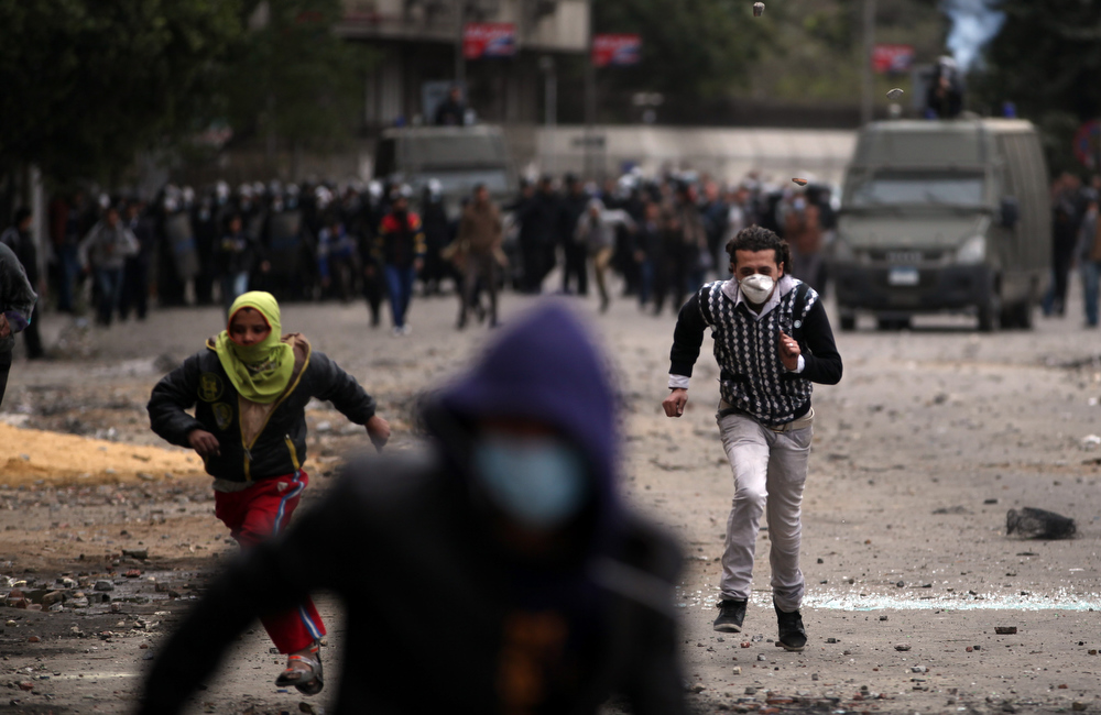Description of . Egyptian protesters run for cover during clashes with riot police near Tahrir Square, Cairo, Egypt, Monday, Jan. 28, 2013. Health and security officials say a protester has been killed in clashes between rock-throwing demonstrators and police near Tahrir Square in central Cairo. The officials say the protester died Monday on the way to the hospital after being shot. (AP Photo/Khalil Hamra)