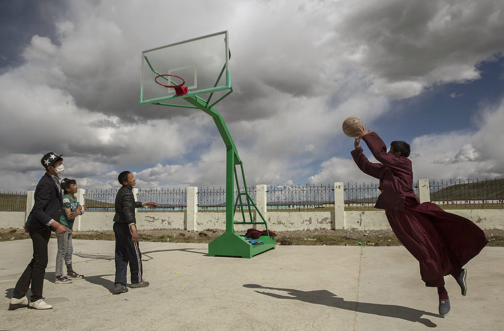 . A Tibetan Buddhist monk leaps as he shoots a basket while playing basketball with friends at a school in  a government resettlement community for former nomads on July 23, 2015 on the Tibetan Plateau in Yushu County, Qinghai, China. Tibetan nomads face many challenges to their traditional way of life including political pressures, forced resettlement by China\'s government, climate change and rapid modernization.  (Photo by Kevin Frayer/Getty Images)