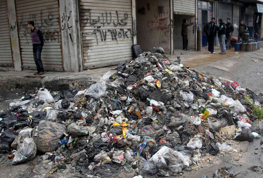 Description of . Men stand near garbage filling a street in Aleppo, February 11, 2013. Doctors in Aleppo and Deir al-Zor have reported outbreaks of leishmaniasis, an endemic tropical disease transmitted by sand-flies that causes skin ulcers resembling leprosy, the World Health Organization (WHO) said. Poor waste management and lack of hygiene have fuelled its spread, but the U.N. agency is trying to deliver medicines to both hotspots, WHO spokesman Glenn Thomas told a news briefing. REUTERS/Muzaffar Salman