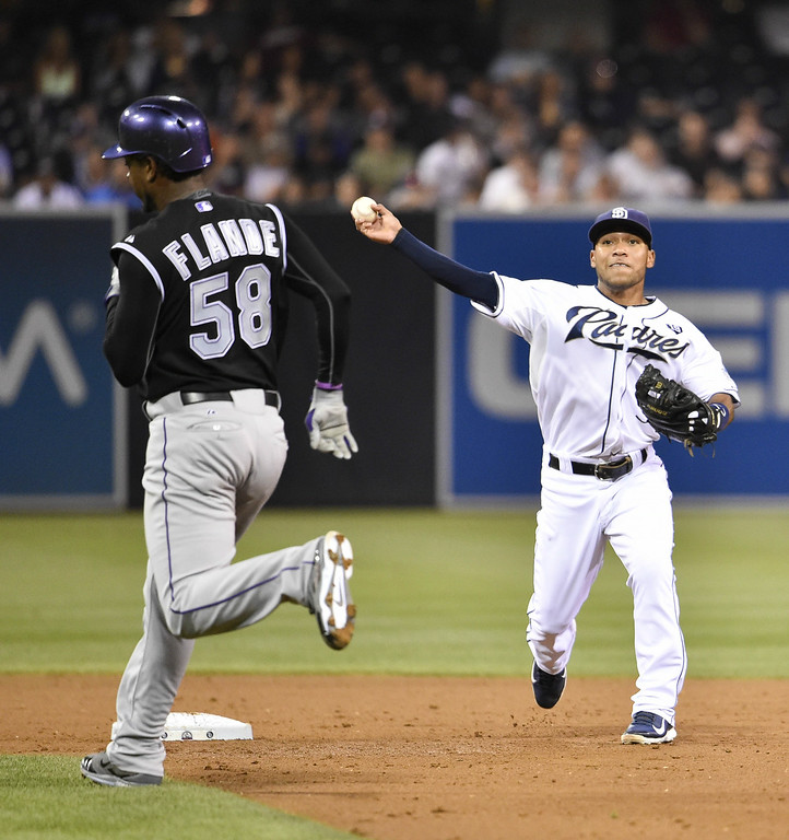 . SAN DIEGO, CA - AUGUST 12:  Alexi Amarista #5 of the San Diego Padres throws over Yohan Flande #58 of the Colorado Rockies as he turns a double play during the third inning of a baseball game at Petco Park August, 12, 2014 in San Diego, California.  (Photo by Denis Poroy/Getty Images)