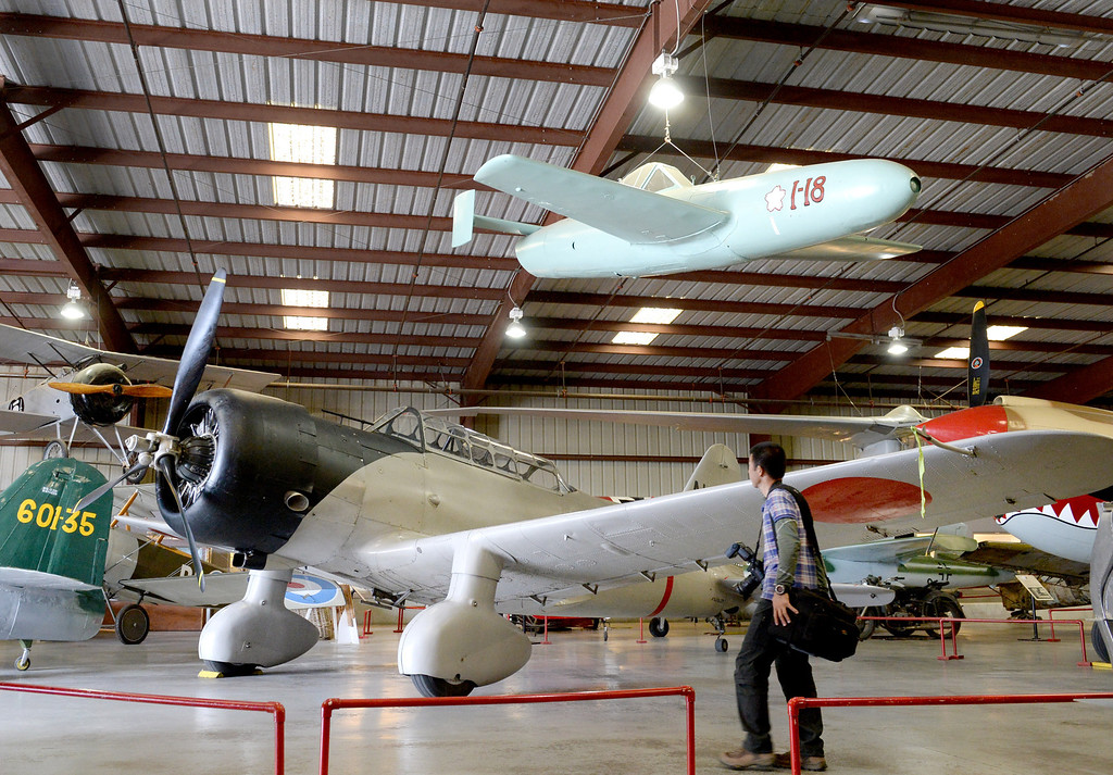 """. Yas Nakanishi of Japan walks by a Aichi D3A \'Val\' dive bomber and Kamikaze aircraft (top), used by the Imperial Navy during World War II, Friday, Dec. 6, 2013. The Museum will present �Attack on Pearl Harbor\' for its monthly Living History Event, which guest speaker Dan king author of the book \""""The Last Zero Fighter\""""."""