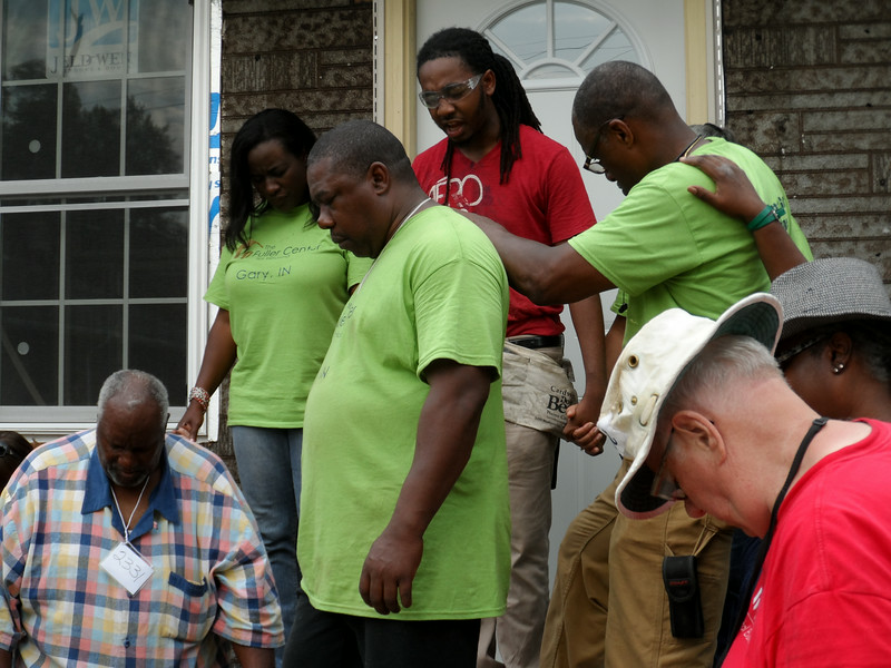 Homeowner partner John Pippins prays during the dedication of his home.