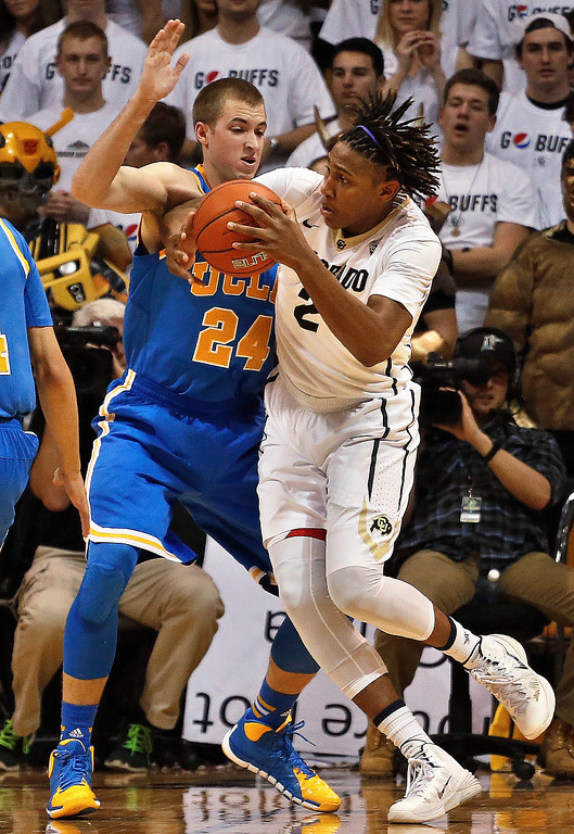 . Colorado\'s Xavier Johnson prepares to shoot as UCLA\'s Travis Wear defends during an NCAA college basketball game in Boulder, Colo., Thursday, Jan. 16, 2014. UCLA won 69-56. (AP Photo/Brennan Linsley)