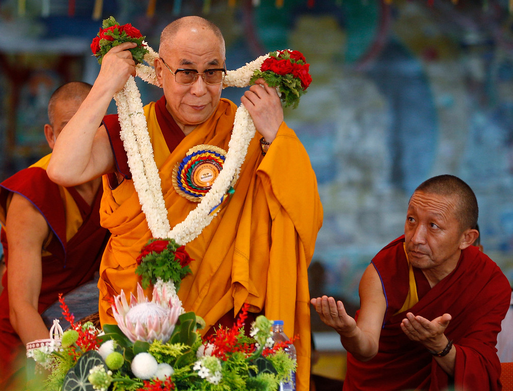 ". Tibetan spiritual leader the Dalai Lama takes off a garland presented to him as a disciple reacts during an event organized to celebrate the Dalai Lama\'s 78th birthday at a Tibetan Buddhist monastery in Bylakuppe, about 220 kilometers (137 miles) southwest of Bangalore, India, Saturday, July 6, 2013. Speaking after an interfaith meeting, he said 150,000 Tibetans living abroad represent ""6 million Tibetans (in China) who have no freedom or opportunity to express what they feel.\"" (AP Photo/Aijaz Rahi)"