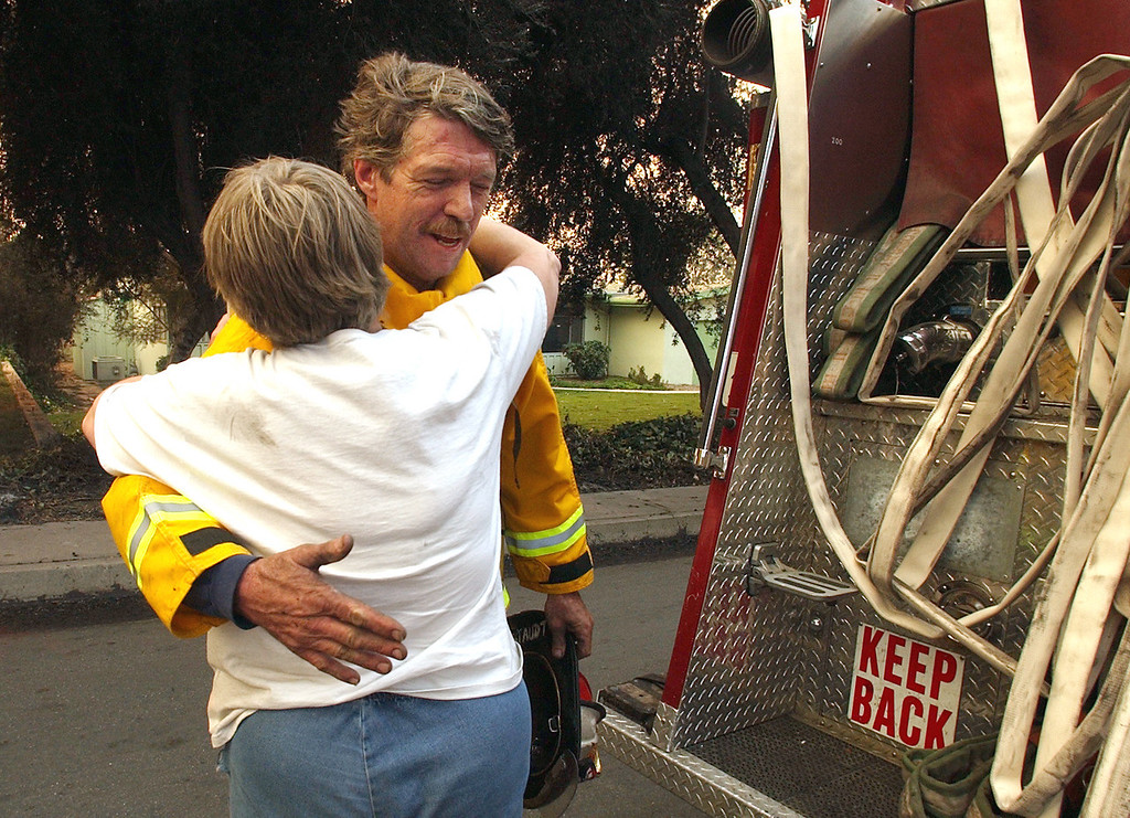. Ten years ago this month the arson caused Old Fire, fanned by Santa Ana winds burned thousands of acres, destroyed hundreds of homes and caused six deaths. The fire burned homes in San Bernardino, Highland, Cedar Glen, Crestline, Running Springs and Lake Arrowhead and forced the evacuation of thousand of residents. San Francisco Fire Department Captain John Staudt is hugged by resident Carol Peterson after Staudt\'s crew hosed out a hot spot in the remains of the Peterson home Sunday morning. The Peterson home was destroyed by the Old Fire Saturday. (Staff file photo/The Sun)