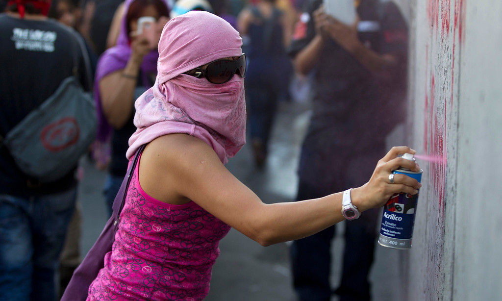 . A masked protester spray paints a wall during a march commemorating the anniversary of the Tlatelolco massacre in Mexico City, Wednesday, Oct. 2, 2013. Mexico commemorated the 45th anniversary of the massacre of students holding an anti-government protest, killed by men with guns and soldiers in 1968, days before the Summer Olympics celebrations in Mexico City. (AP Photo/Eduardo Verdugo)