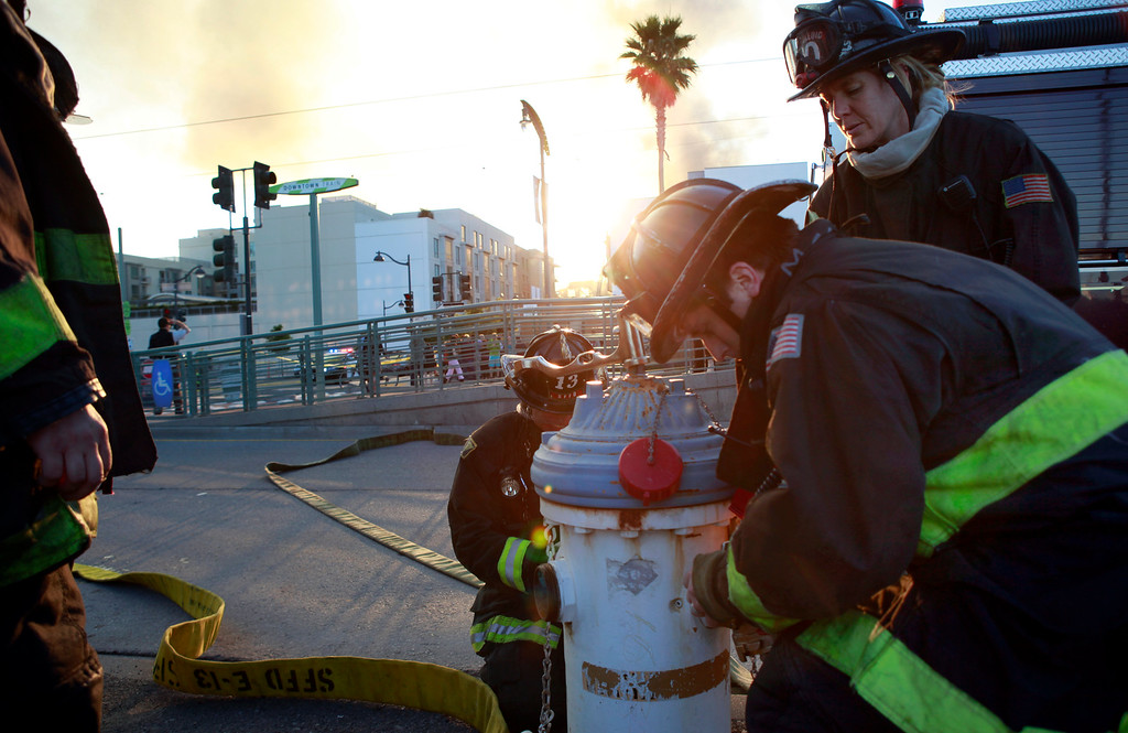 . Firefighters tap a hydrant on Third Street in San Francisco to battle a fire at a multi-story residential building under construction in the Mission Bay neighborhood of San Francisco, Calif., Tuesday evening, March 11, 2014. (Karl Mondon/Bay Area News Group)
