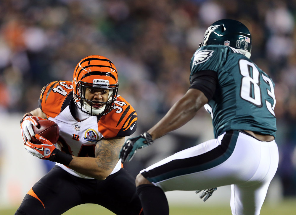 . Dan Herron #34 of the Cincinnati Bengals carries the ball as  Marvin McNutt #83 of the Philadelphia Eagles defends on December 13, 2012 at Lincoln Financial Field in Philadelphia, Pennsylvania. Herron recovered a blocked punt. (Photo by Elsa/Getty Images)