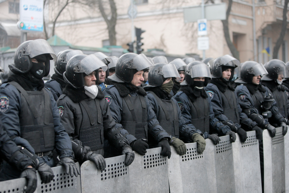 Description of . Police officers block a street near the Cabinet of Ministers offies in the center of Kiev, Ukraine, Thursday, Feb. 20, 2014. Fierce clashes between police and protesters, some including gunfire, shattered a brief truce in Ukraine's besieged capital Thursday, killing numerous people. The deaths came in a new eruption of violence just hours after the country's embattled president and the opposition leaders demanding his resignation called for a truce and negotiations to try to resolve Ukraine's political crisis. (AP Photo/Efrem Lukatsky)