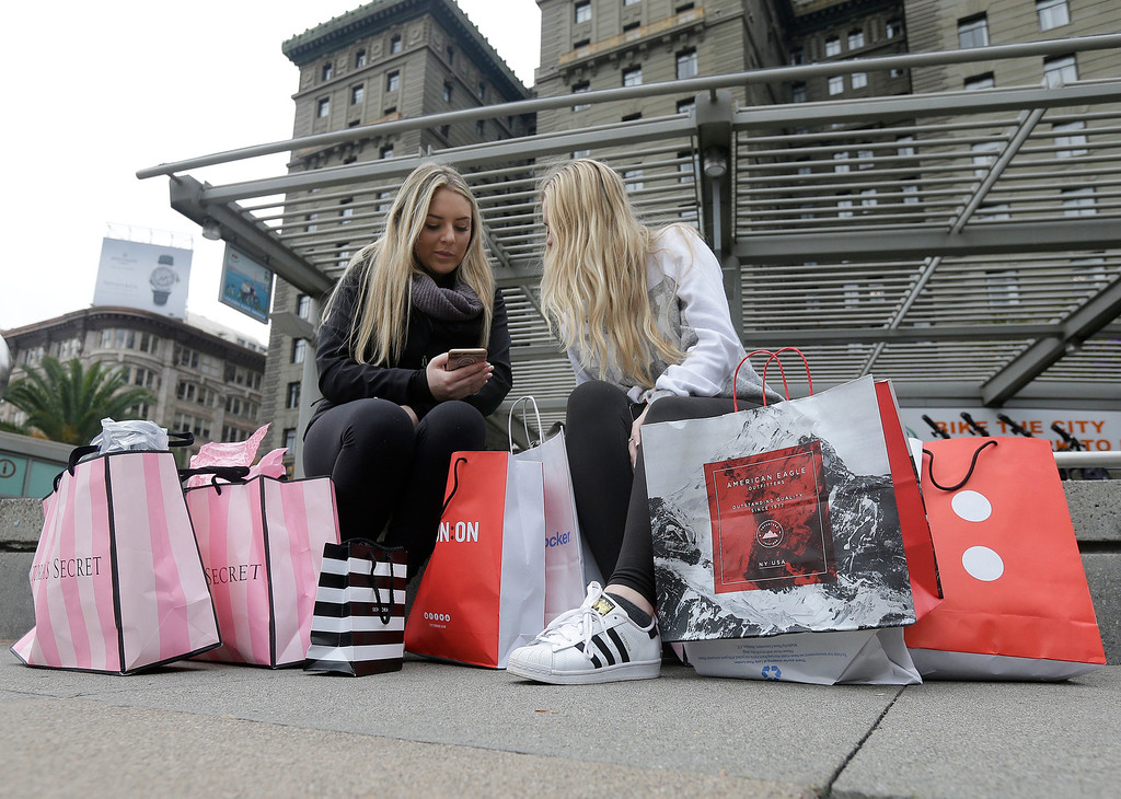 . Maddy, left, and her friend Maggie, last names not given, sit with their shopping bags at Union Square in San Francisco, Friday, Nov. 25, 2016. Black Friday, historically the starting line of the retail industry\'s crucial holiday buying season, isn\'t quite the one-day spree it used to be. Some retailers have pushed their biggest Black Friday door-buster deals into Thanksgiving Day and spread other promotions to even earlier in the season. (AP Photo/Jeff Chiu)