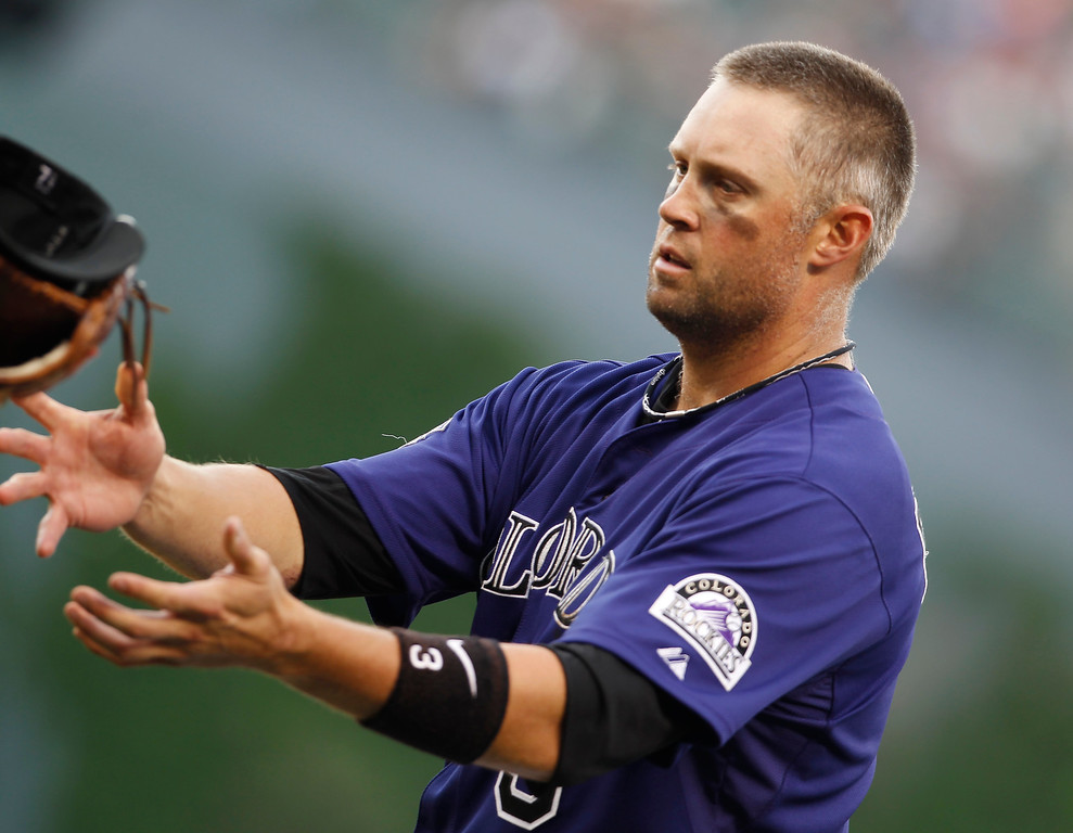 . Colorado Rockies\' Michael Cuddyer tosses his batting equipment after grounding out against the Washington Nationals to end the eighth inning of a baseball game in Denver on Thursday, June 13, 2013. The Nationals won 5-4. (AP Photo/David Zalubowski)