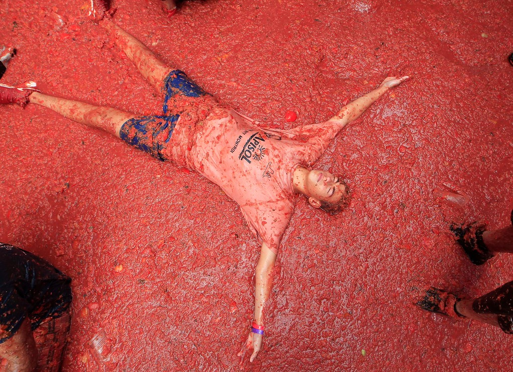 ". A men lies in a puddle of squashed tomatoes during the annual ""Tomatina\"", tomato fight fiesta, in the village of Bunol, 50 kilometers outside Valencia, Spain, Wednesday, Aug. 30, 2017. The streets of an eastern Spanish town are awash with red pulp as thousands of people pelt each other with tomatoes in the annual \""Tomatina\"" battle that has become a major tourist attraction. At the annual fiesta in Bunol on Wednesday, trucks dumped 160 tons of tomatoes for some 20,000 participants, many from abroad, to throw during the hour-long morning festivities. (AP Photo/Alberto Saiz)"