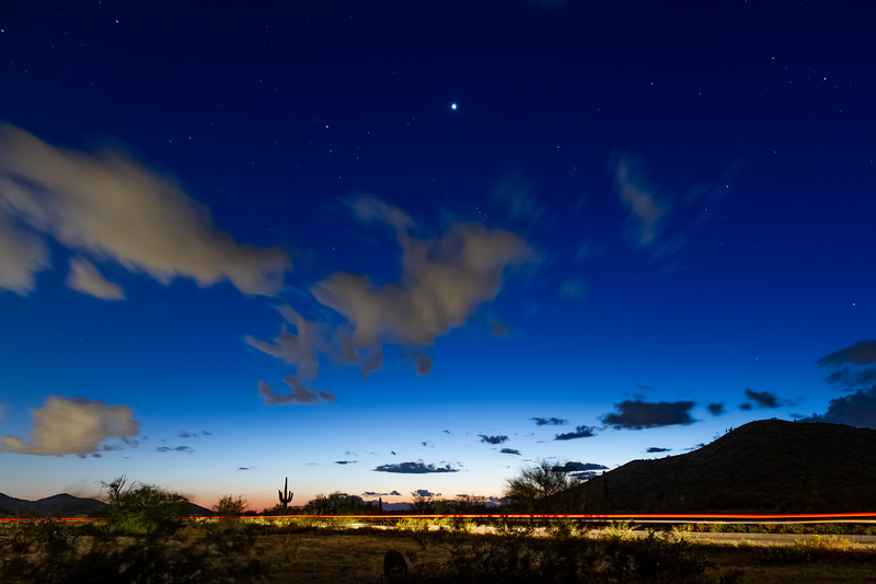 Evening image of the desert night sky during the blue hour with dramatic clouds and stars
