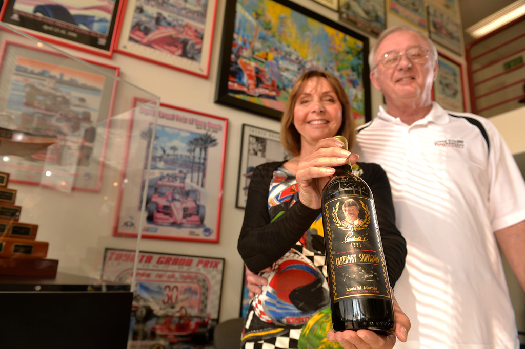 . Volunteers Gary and Phyllis Halliday hold a bottle of wine that Mario Andretti signed, volunteers are what power the Grand Prix Foundation, the charitable arm that hosts two major fundraising events in conjunction with the Toyota Grand Prix of Long Beach in Long Beach, CA. Monday February 17, 2014. (Thomas R. Cordova Daily Breeze/Press-Telegram)