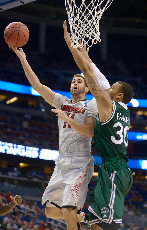 . Louisville forward Luke Hancock (11) aims for the basket as Manhattan forward Ashton Pankey (30) defends during the first half in a second-round game in the NCAA college basketball tournament Thursday, March 20, 2014, in Orlando, Fla. (AP Photo/Phelan M. Ebenhack)